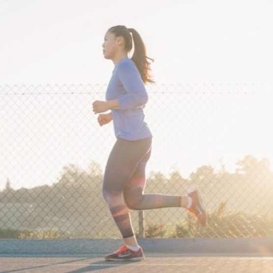 photo of a woman running with a sunny background