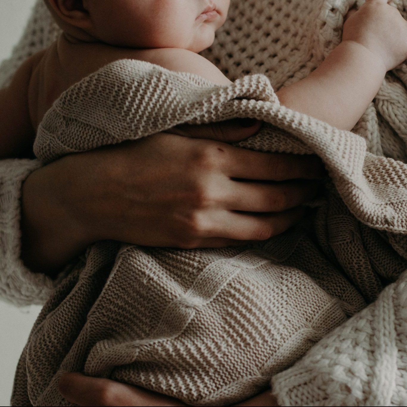 a newborn baby wrapped in a cream blanket, being held